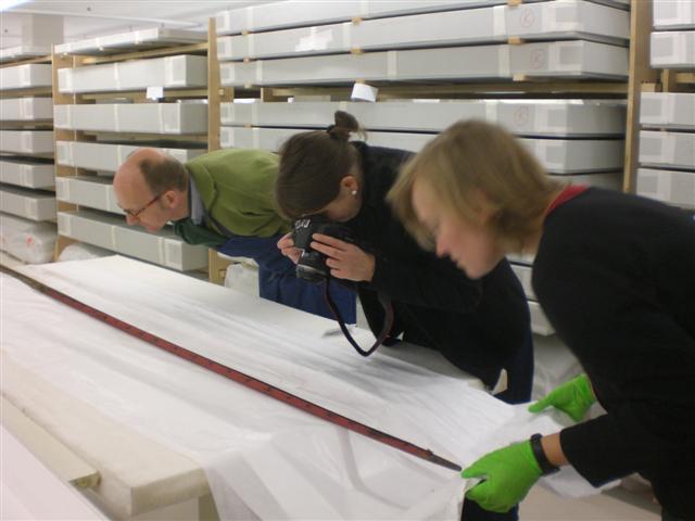 historisches museum frankfurt: Vorsichtige Begutachtung einer Fahnenstange und Dokumentation im Depot