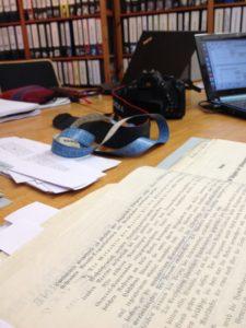 Blick auf Tisch im Lesesaal mit den wichtigsten Worktools: Maßband, Kamera, Laptop.