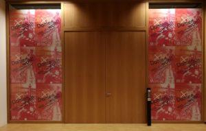 Blick auf die geschlossenen Tür mit Ausstellungsplakaten