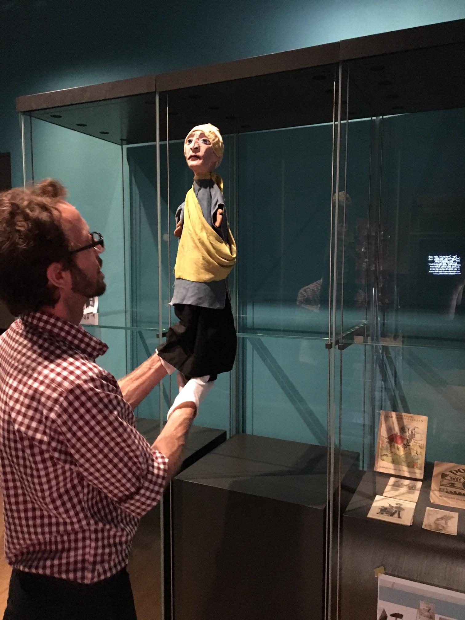 Restaurator stellt eine Puppe in die Vitrine
