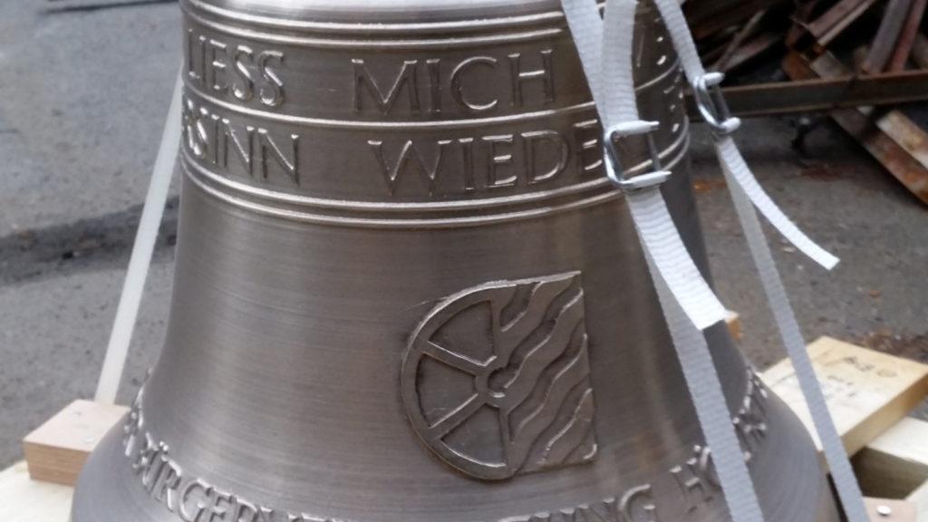 Glocke mit Transportriemen steht auf einer Holzpalette