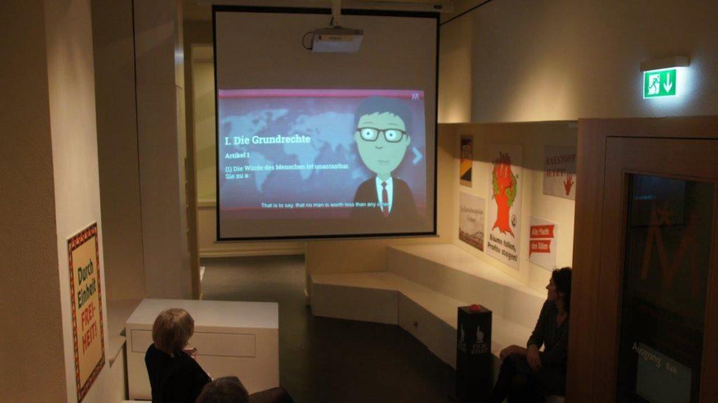 Blick auf Videoleinwand mit Grundrechten, vorne die Gruppe