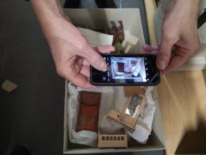jemand fotografiert mit einem handy eine volle Objektkiste