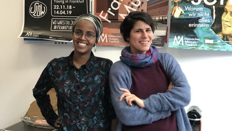 die beiden Agentinnen für Diversität stehen vor einer Wand mit Museumsplakaten