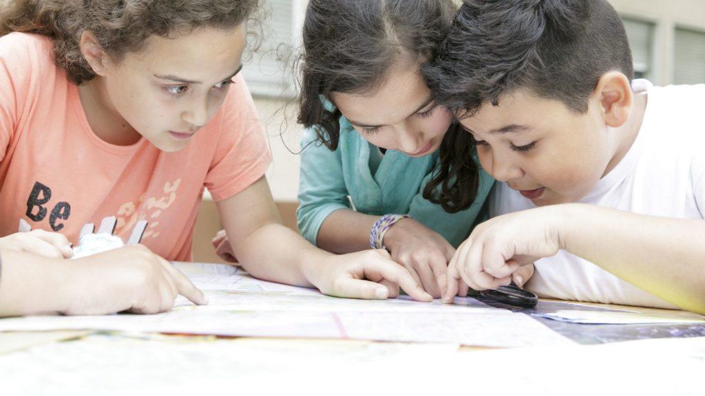 drei Kinder schauen auf einen Plan