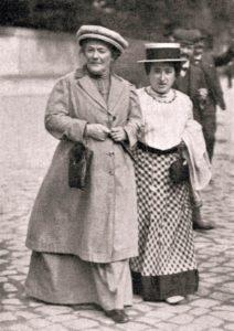 schwarz-weiß-Fotografie mit den beiden Frauen, die Arm in Arm auf einer Strasse gehen