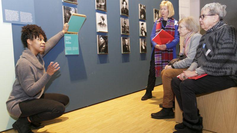 Personen in der Ausstellung vor Fotografien