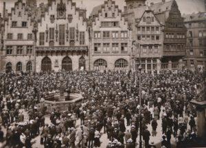 schwarz-weiß-Fotografie mit einer Menschenmenge auf dem Römerberg, vor dem Rathaus in Frankfurt