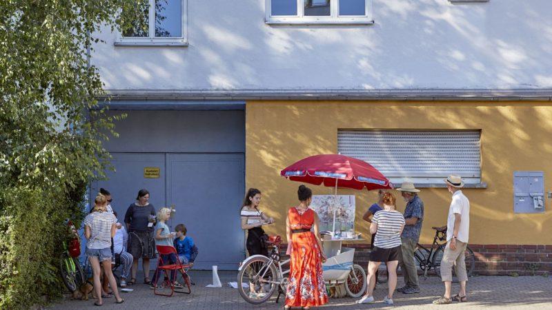 menschen stehe in Sommerkleidung um das Lastenfahrrad des Museums