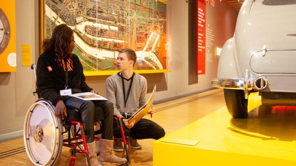 eine Frau im Rollstuhl und ein mann sitzen vor einem hafenmodell im Museum
