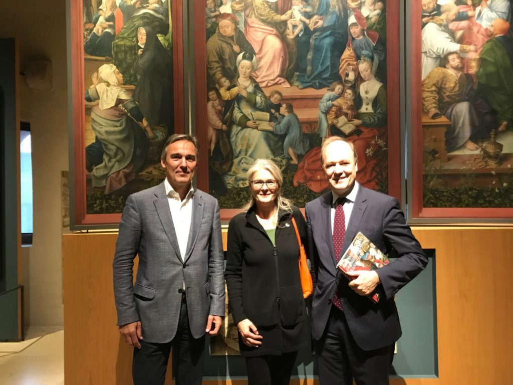 zwei Männer und eine Frau stehen vor einem Altarbild
