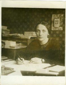 schwarz-weiss-Foto: eine Dame sitzt am Schreibtisch, sie hat einen Stift in der Hand, vor ihr liegt Papier
