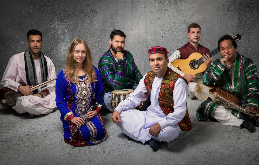 Musiker*innen sitzen in bunter Kleidung auf dem Boden