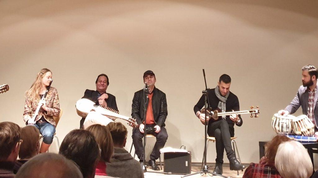 die Musiker*innen sitzen auf einer Bühne