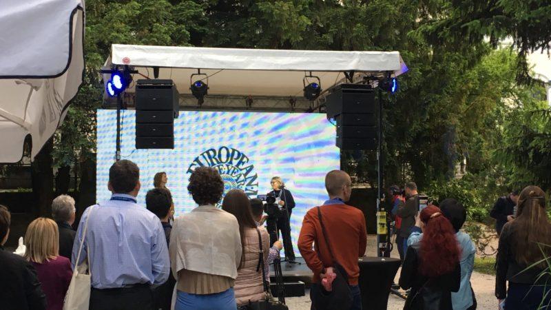 Menschen stehen vor einer Bühne im Park