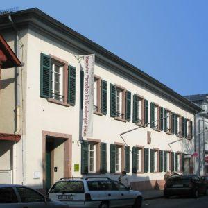 Die Fassade eines zweigeschössigen, weiß gestrichenen Gebäudes mit grünen Festerläden. Davor eine Straße mit Autos