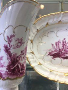 Eine Kanne und ein Teller mit purpurnen mythologischen Szenen bemalt