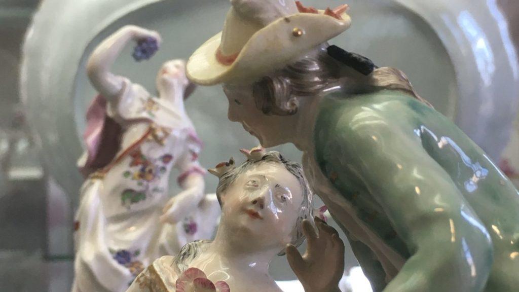 Detail zweier, einander zugewandter Porzellanfiguren. Eine Frau sitzt und blick zu einem Mann der Blumen in einem Korb hält