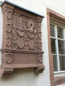 Wappenstein aus rotem Sandstein neben einem Fenster in die Fassade des Hauses eingelassen.