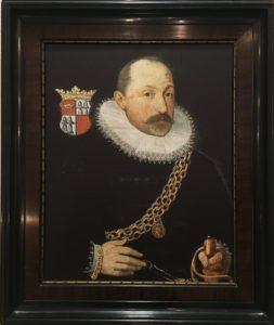 Die Kopie eines Gemäldes, es zeigt eine Halbfigur die den Betrachter im dreiviertel Profil ansieht. Der Mann ist schwarz gekleidet und trägt eine weißen Spitzenkragen, außerdem eine Goldkette über der Brust. Im Hintergrund sieht man ein Wappen