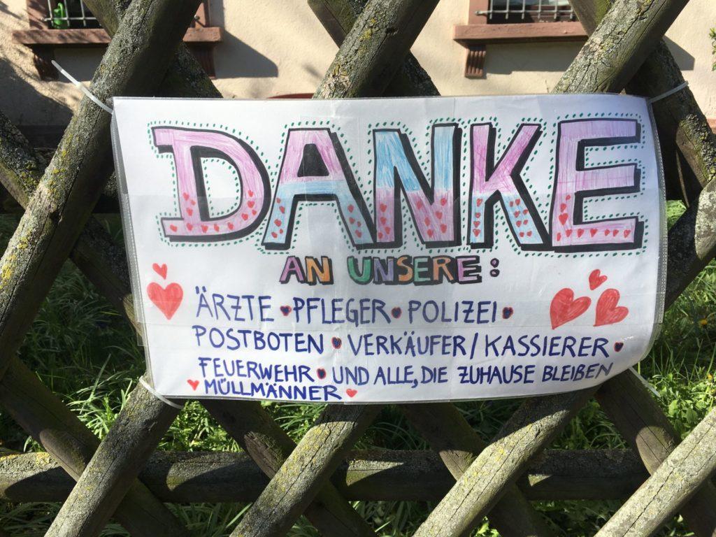 Buntes Schild, auf dem steht: Danke an unsere Ärzte, pfleger, Polizei, postboten, verkäufer/kassierer Feuerwehr und alle, die zuhause bleiben