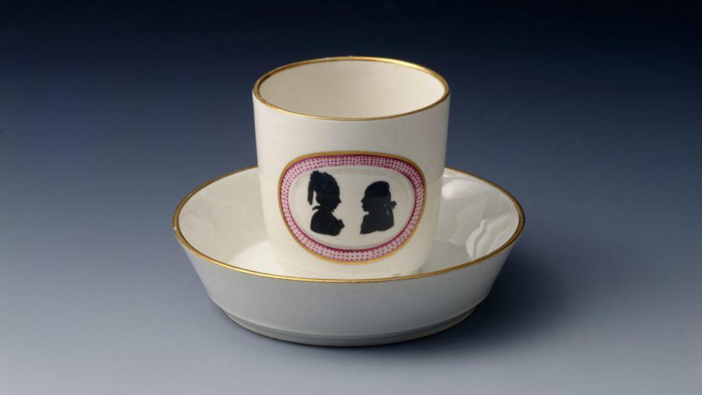 Tasse mit Untertasse, auf der Tasse zwei Menschen in profil
