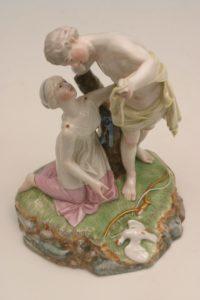 Zwei antikisierende Porzellanfiguren, die weibliche Figur kniet vor der männlichen, auf dem Boden eine tote Taube