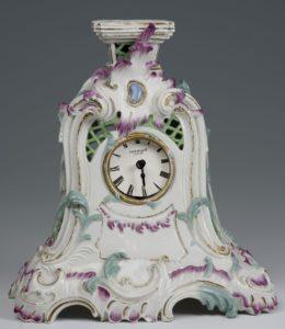 Uhrengehäuse aus Porzellan mit geschwungener, floraler Dekoration in grün und rosa