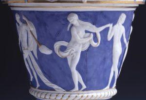 Auf dem blauen Grund des Mittelfeldes ist ein Figurenfries mit antikischen Gestalten modelliert. Zu sehen sind zwei Jünglinge vier tanzende Nymphen und zwei Putten.