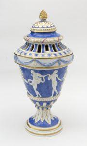 Porzellanvase des Klassizismus, blaugründig mit einem weißen antikisierenden Relief auf dem Vasenbauch, viele blaue und goldene Verzierungen