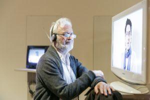 """Ein Besucher hört sich ein Interview aus der Installation """"Generation 1,5"""" an."""