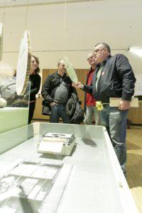 """Der Leihgeber einer Schreibmaschine betrachtet mit Ausstellungsbesuchern die """"Frankfurter Geschichten"""""""