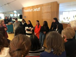 """In einem Gespräch stellen Jugendliche ihre Arbeit """"Stimmen der Migration"""" Ausstellungsbesucher*innen vor."""