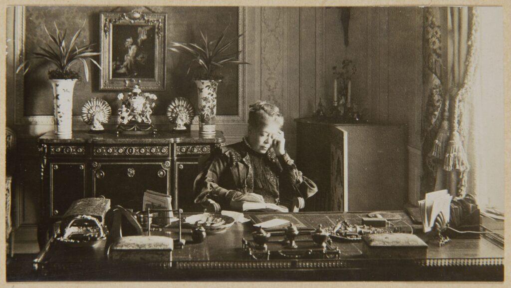 Ein historische schwarzweißfoto: eine Frau sitzt an einem Schreibtisch und liest. Hinter Ihr stehen auf einem Kaminsims Blumen und Porzellangegenstände