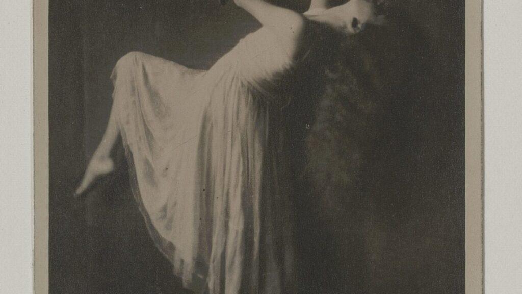 Schwarzweiß-Fotografie mit einer Tänzerin im weißen Kleid. Sie beugt sich nach hinten, und hat das linke Knie angebeugt und den rechten Arm nach oben ausgestreckt.