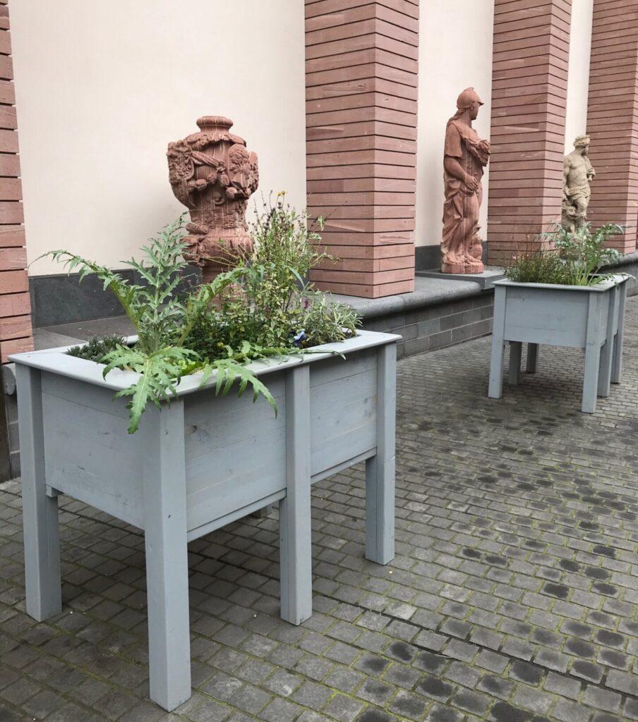 Blick auf ein graues Hochbeet mit grünen Pflanzen, im Hintergrund stehen Gartenskulpturen