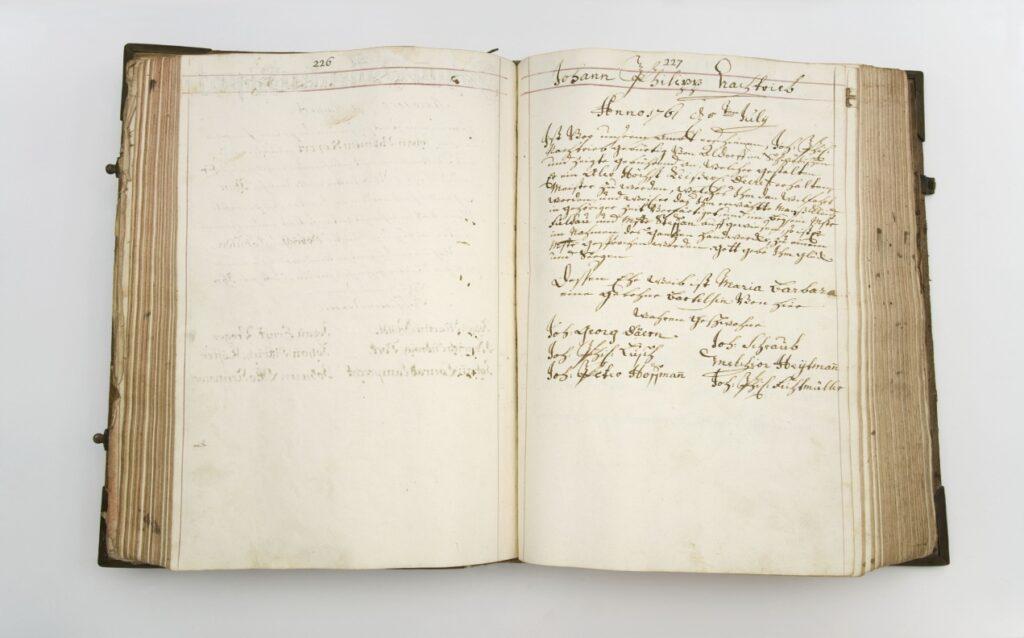 aufgeschlagenes Buch mit einer alten Handschrift auf der rechten Seite