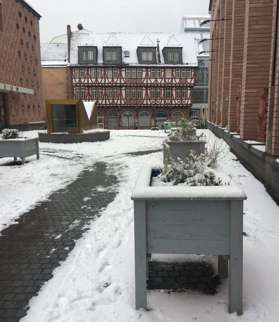 Blick auf den Museumsplatz. Die grauen Hochbeete und der Boden sind mit Schnee bedeckt. Im hintergrund sieht man ein Fachwerkhaus