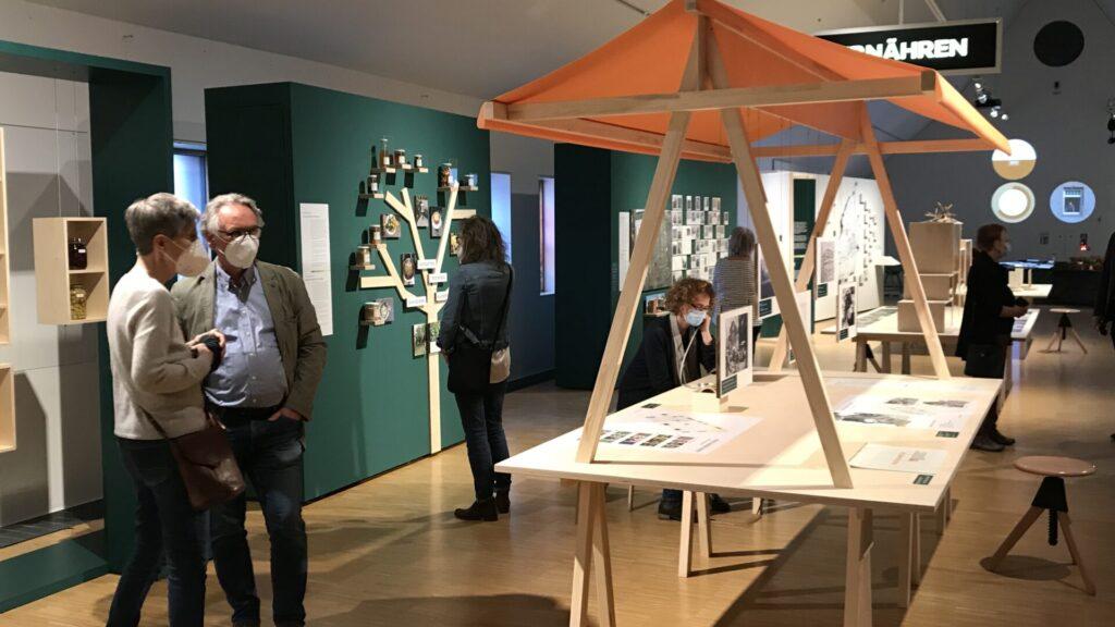 Blick in die Ausstellung mit einem Holzelement mit Schirmdach; es stehen einige Personen da, mit Maske