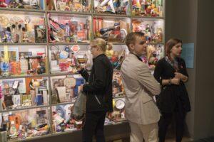 Besucher*innen stehen vor dem Kunstwerk und schauen in das Objektregal