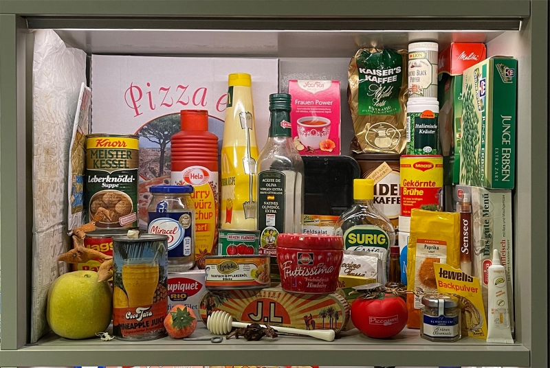 """Objektvitrine """"Dosen, Früchte, Kaffee, Tee mit vielen Objekten aus der Küche"""
