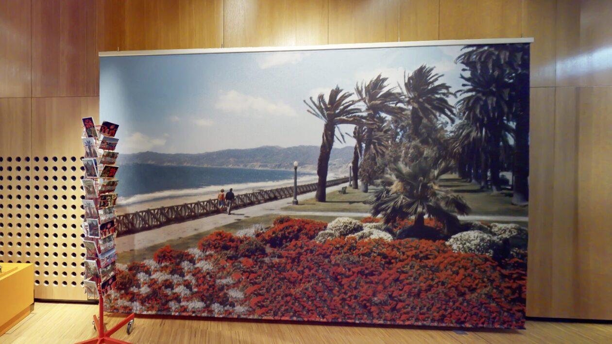 ein riesiges Transparent mit geranien und Palmen am meer, davor ein Postkartenhalter