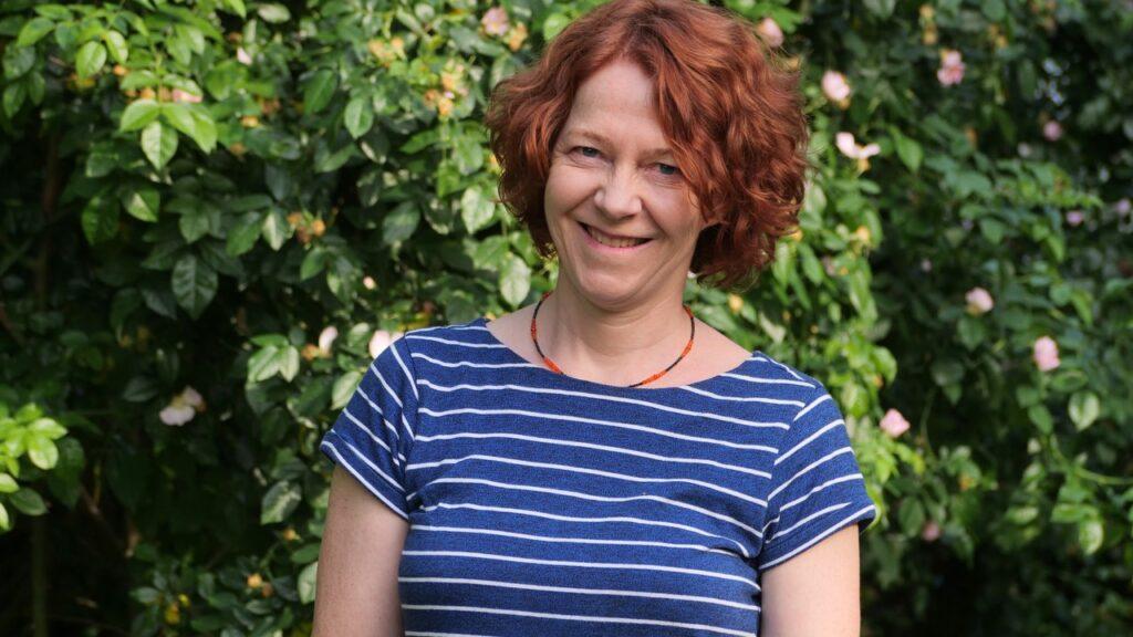 Frau in einem blauen Ringelshirt vor einem grünen Strauch